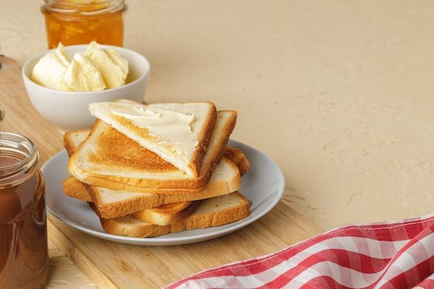 Kromka świeżego chleba z masłem i dżemem na stole