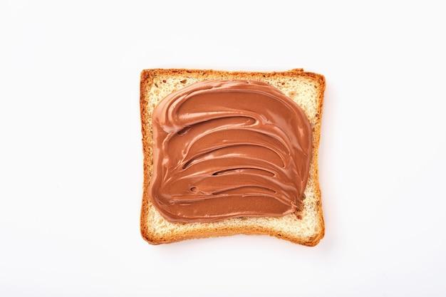 Kromka tostów z kremem czekoladowym z orzechami laskowymi na białym tle na białym tle ze ścieżką przycinającą