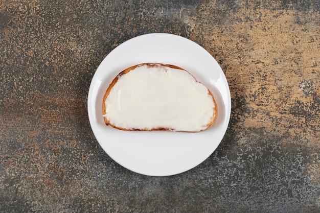 Kromka tostów ze śmietaną na białym talerzu.