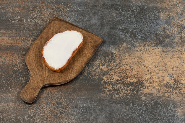 Kromka tostów ze śmietaną na desce.