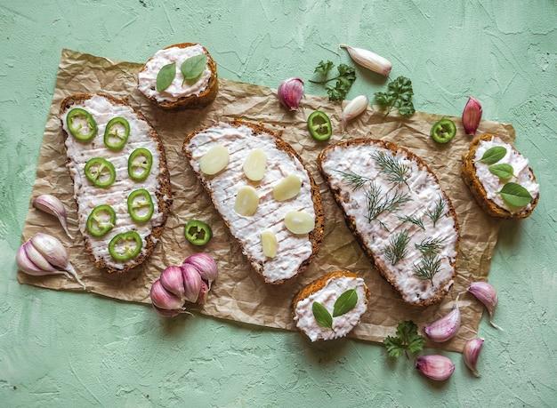 Kromki bagietki czosnkowej, masło czosnkowe, zioła