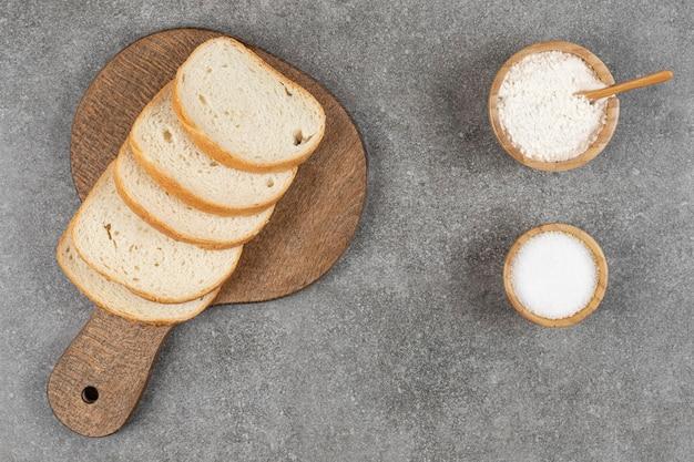 Kromki białego chleba na desce z solą i mąką