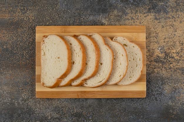 Kromki białego chleba na desce.