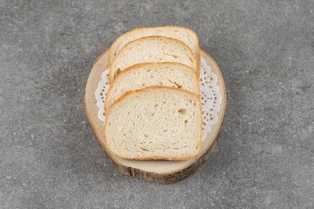 Kromki białego chleba na marmurze.
