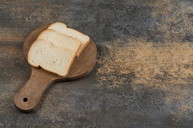 Kromki białego chleba tostowego na drewnianą deskę do krojenia.
