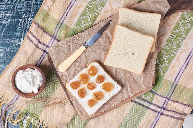 Kromki białego chleba ze śmietaną i konfiturą.