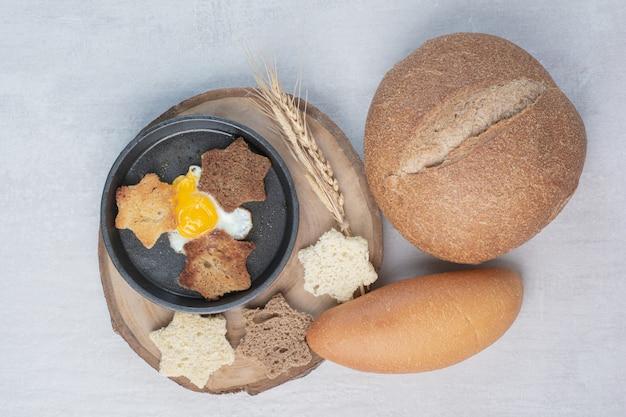 Kromki białego i ciemnego pieczywa z jajkiem sadzonym na drewnianym talerzu.