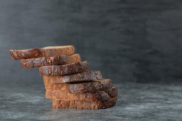 Kromki brązowego świeżego chleba na szarym tle.