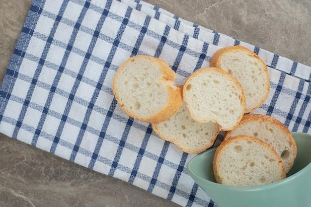 Kromki chleba bagietki z miski na obrus. wysokiej jakości zdjęcie