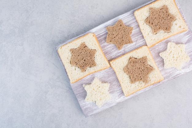 Kromki chleba czarno-białe w kształcie gwiazdy i kwadratu na drewnianym talerzu