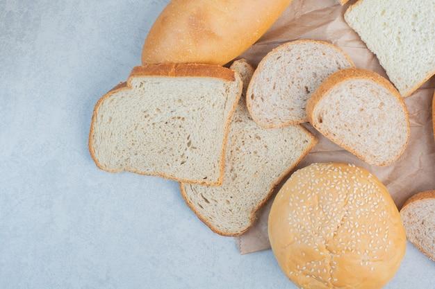 Kromki chleba i bułka z sezamem na niebieskim tle. wysokiej jakości zdjęcie