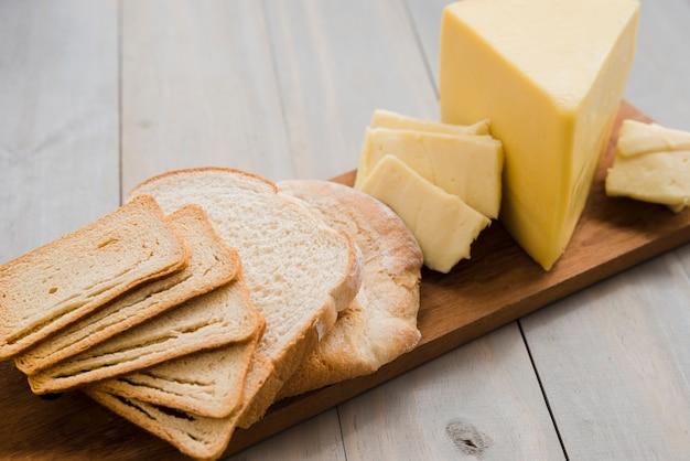 Kromki chleba i kliny serowe na desce do krojenia nad stołem