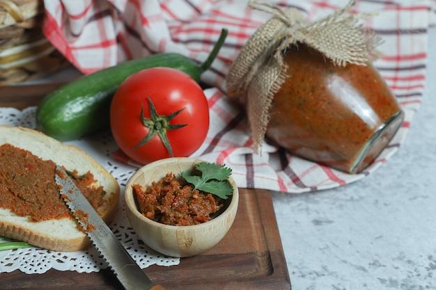 Kromki chleba i makaron pomidorowy na kamiennej powierzchni.