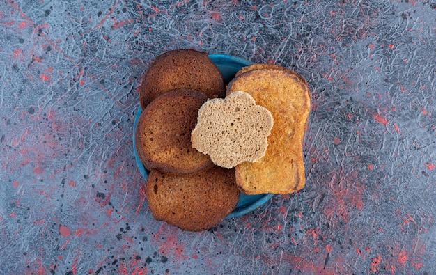 Kromki chleba na białym tle na niebieskim talerzu.