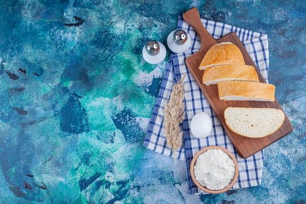 Kromki chleba na desce obok jajka na twardo i miskę mąki na ręcznik, na niebieskim tle.