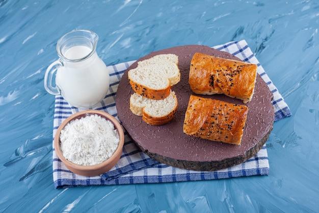 Kromki chleba na desce obok jajka na twardo i miski mąki na ręczniku, na niebieskiej powierzchni.