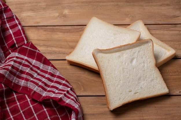 Kromki chleba na drewnianym stole w tle