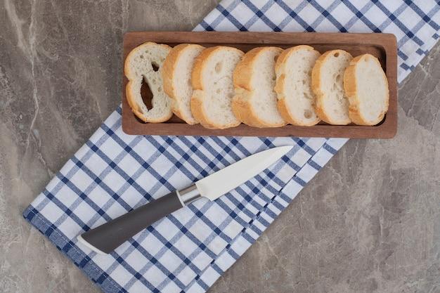 Kromki chleba na drewnianym talerzu z nożem. wysokiej jakości zdjęcie