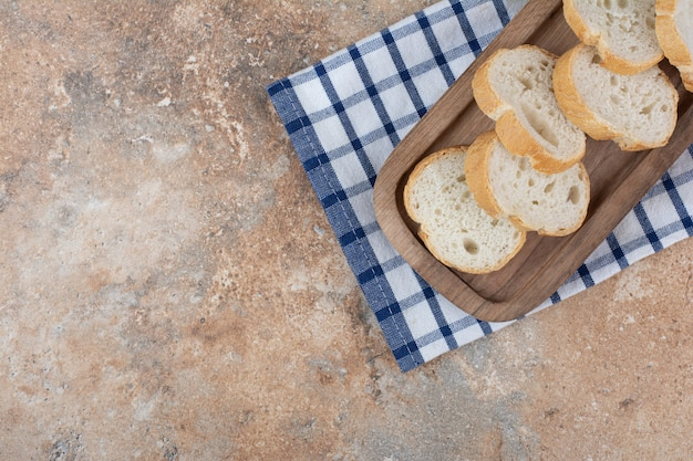Kromki chleba na drewnianym talerzu z obrusem
