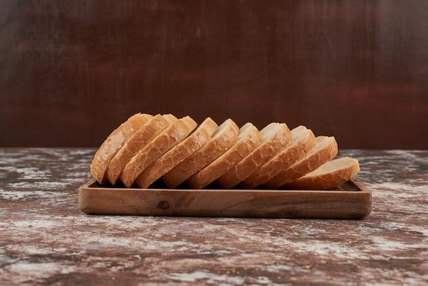 Kromki chleba na drewnianym talerzu.
