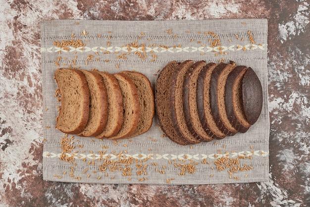 Kromki chleba na marmurze na ręczniku.