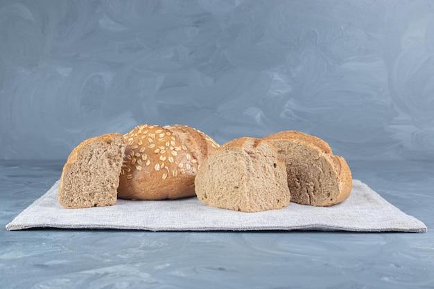 Kromki chleba na złożonym obrusie na marmurowym stole.