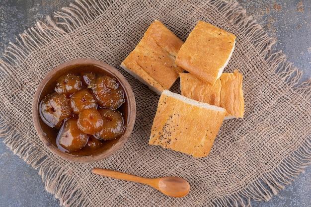 Kromki chleba podawane z filiżanką konfitury figowej
