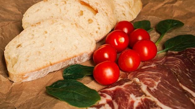 Kromki chleba, pomidorki koktajlowe, szpinak i szynka. składniki na kanapkę lub bruschettę. zdrowe gotowanie świeżej żywności