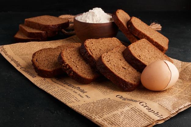 Kromki chleba, szklanka mąki i jajko na kawałku gazety.