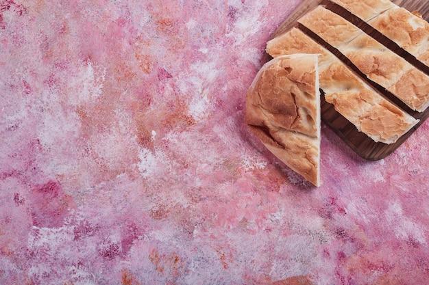 Kromki chleba tandir na różowym stole.