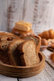 Kromki chleba umieszczone w drewnianym talerzu na białym drewnianym stole.