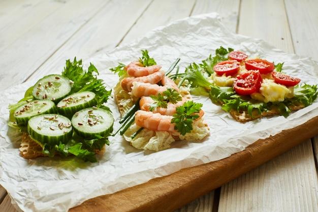 Kromki chleba waflowego z różnymi warzywami, krewetkami i przyprawami