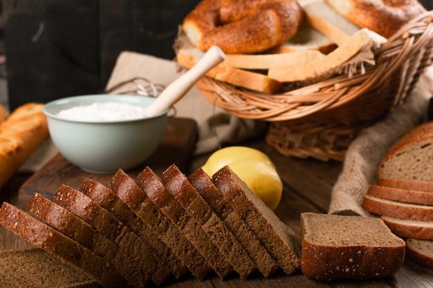 Kromki chleba z bułkami i miską mąki
