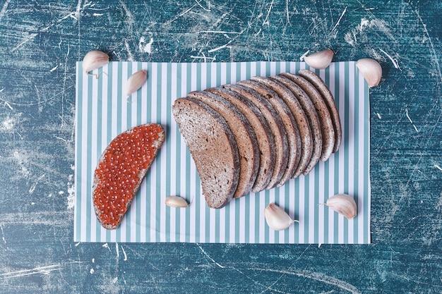 Kromki chleba z czosnkiem i kawiorem na niebieskim stole.