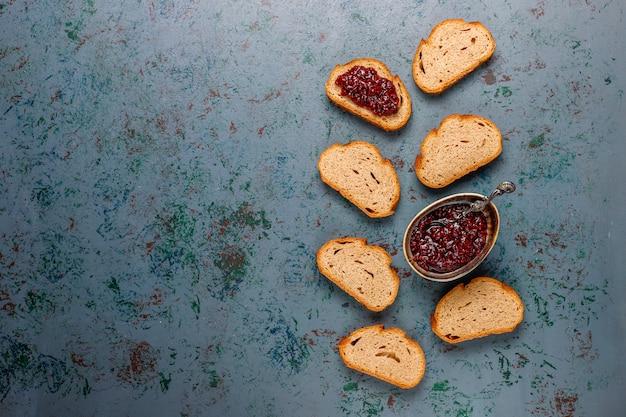 Kromki chleba z dżemem malinowym, łatwe zdrowe przekąski, widok z góry