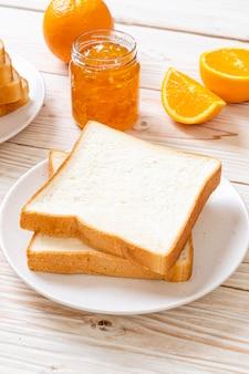 Kromki chleba z dżemem pomarańczowym na śniadanie