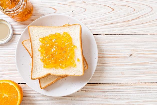 Kromki chleba z dżemem pomarańczowym
