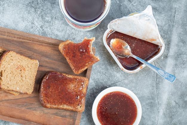 Kromki chleba z dżemem truskawkowym na drewnianej desce do krojenia.