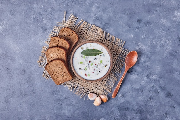 Kromki chleba z filiżanką zupy jogurtowej i czosnku, widok z góry.