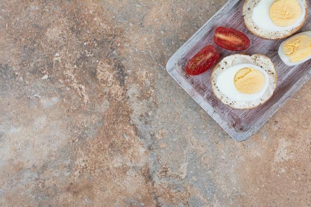 Kromki chleba z jajkami na twardo i plastrami pomidora na desce