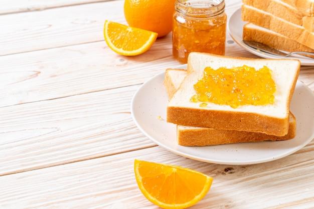 Kromki chleba z konfiturą pomarańczową i pomarańczami