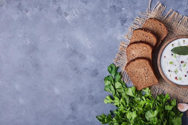 Kromki chleba z kubkiem zupy jogurtowej, pietruszki i czosnku.