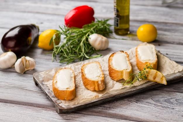 Kromki chleba z masłem. grillowana cytryna i zielone zioło. zdrowe jedzenie na obiad. podstawowy składnik do kanapek.