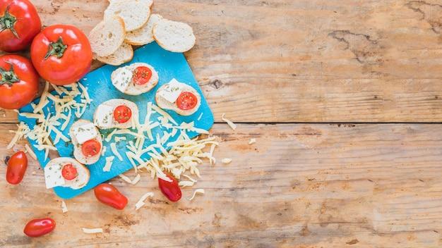 Kromki chleba z pomidorami i tartym serem na drewnianym stole