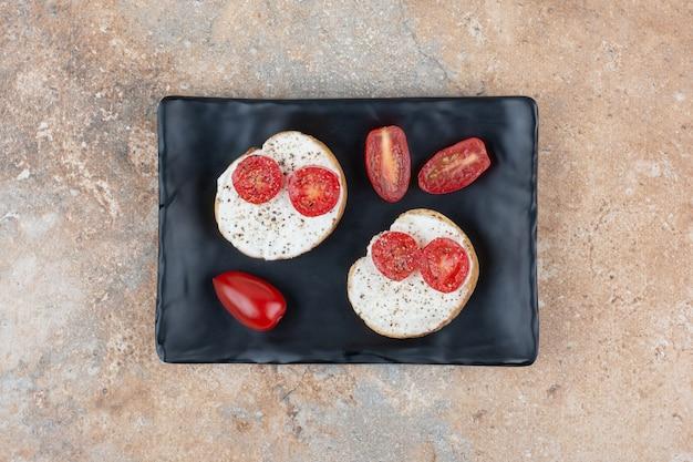 Kromki chleba ze śmietaną i pomidorem na czarnym talerzu