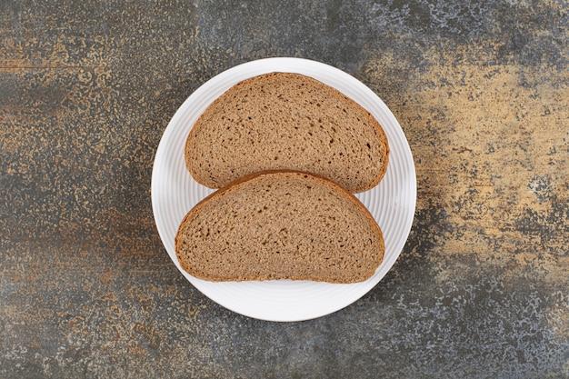 Kromki chleba żytniego na białym talerzu.