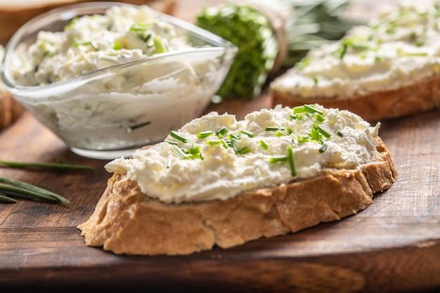 Kromki chrupiącego chleba i szklana miska z kremem serowym i pokrojonym szczypiorkiem na starej drewnianej desce do krojenia.