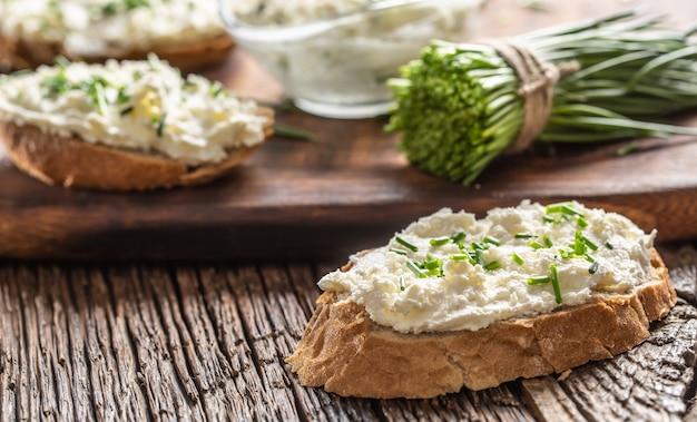 Kromki chrupiącego chleba z kremem serowym i świeżo pokrojonym szczypiorkiem na starej drewnianej desce do krojenia.