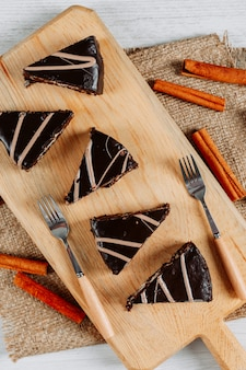 Kromki ciasta czekoladowego w drewnianej desce i kawałek worka z cynamonem i widelcami wysoki kąt widzenia na białym tle