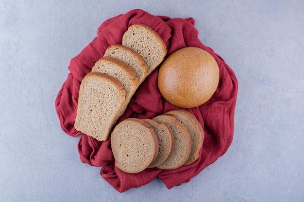 Kromki ciemnego chleba i bułka na kawałku tkaniny na marmurowej powierzchni